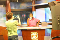Jazmyn Webb poses at the news desk of WWMT after a visit to the studio with the Travel Writers.