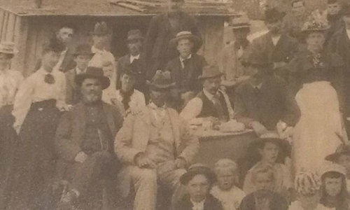 Benjamin Losford sits in the center of this photo along with other men of Edmore, Michigan. Benjamin came to the town just before it became incorporated in 1878 as the town's first barber and first African American citizen. Photo by Pine Forest Historical Museum in Edmore, Michigan.